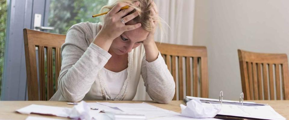Woman sits at table with head in hands, looking at pile of bills