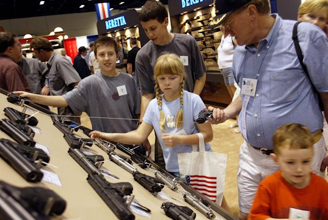 Members of a family check out the Beretta gun display at the 132nd Annual National Rifle Association Meeting in Orlando, Florida, April 27, 2003. The National Rifle Association had plenty to celebrate at its annual convention on Sunday: a gun-friendly president and Congress it helped elect, a robust membership of four million and a real shot at eliminating its most hated law - the ban on assault weapons. PP03040078 REUTERS/Shannon Stapleton SS/HB NRA
