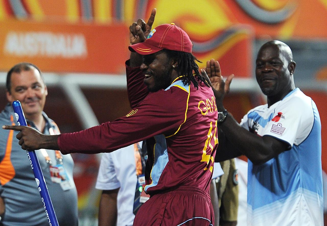 West Indies cricketer Chris Gayle (L) and Coach Ottis Gibson (R) dance after victory in the ICC Twenty Cricket World Cup's semi-final match between West Indies and Australia at the R. Premadasa International Cricket Stadium in Colombo on October 5, 2012. AFP PHOTO/ LAKRUWAN WANNIARACHCHI