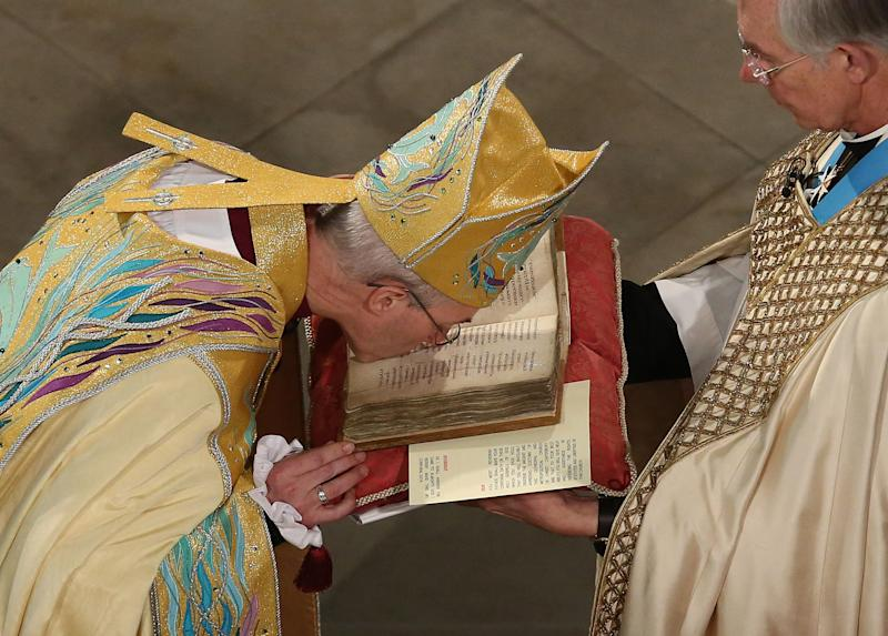 The new Archbishop of Canterbury Justin Welby, left, kisses the Canterbury Gospels during his enthronement service at Canterbury Cathedral in Canterbury England Thursday March 21, 2013. (AP Photo/ Gareth Fuller/Pool)