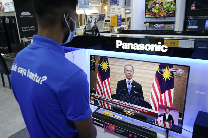 An electronic shop worker wearing a face mask watches a live broadcast of Malaysian Prime Minister Muhyiddin Yassin at a shopping outlet in Kuala Lumpur, Malaysia, Tuesday, Jan. 12, 2021. Malaysia's king Tuesday approved a coronavirus emergency that will prorogue parliament and halt any bids to seek a general election in a political reprieve for embattled Muhyiddin. (AP Photo/Vincent Thian)
