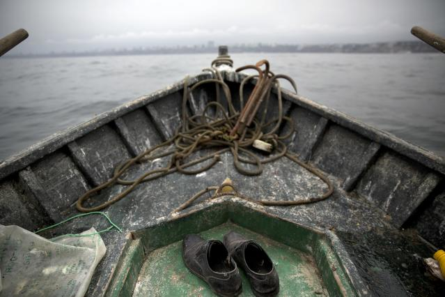 <p>The shoes of small-scale fisherman Alvaro del Carmen, 51, are seen on the deck of his boat near Chorrillos harbor in Lima, Peru, on Sept. 23, 2015. (Photo: Rodrigo Abd/AP) </p>