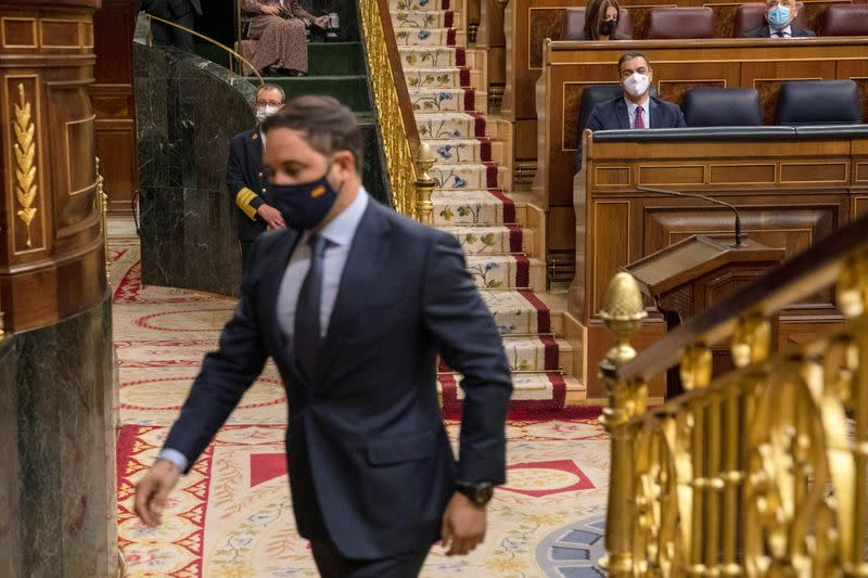 Santiago Abascal, leader of far-right party Vox, walks to give his speech as Spain Prime Minister Pedro Sanchez looks on during a no confidence motion against the government at parliament in Madrid