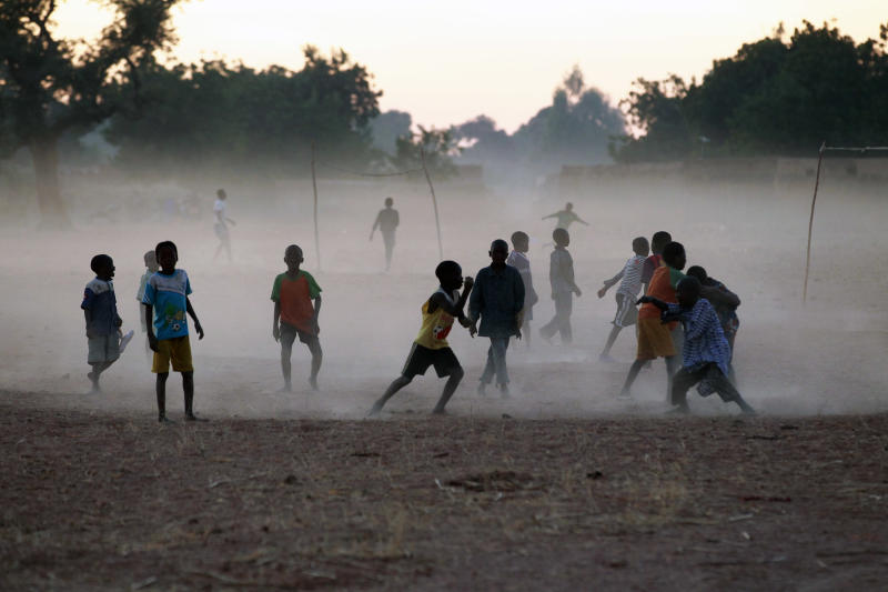Children and adults alike play soccer on a dusty field in Segou, central Mali, some 240km (140 miles) from Bamako Monday Jan. 21, 2013. French troops in armored personnel carriers rolled through the streets of Diabaly on Monday, winning praise from residents of this besieged town after Malian forces retook control of it with French help a week after radical Islamists invaded. The Islamists also have deserted the town of Douentza, which they had held since September, according to a local official who said French and Malian forces arrived there on Monday as well. (AP Photo/Jerome Delay)