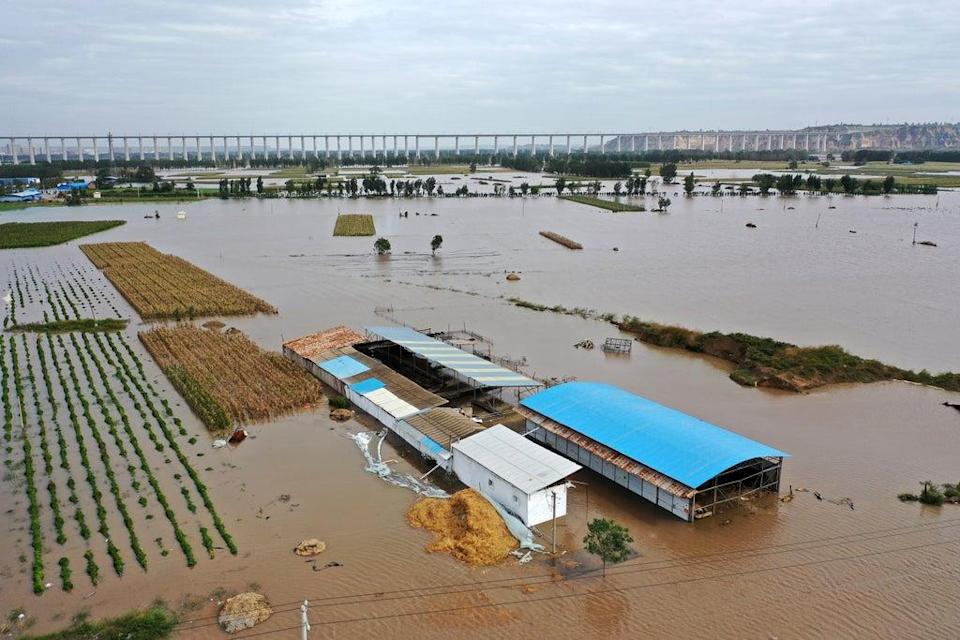 In this photo released by Xinhua News Agency, an aerial photo shows an overflowing river in Shanxi province's Hejin city (AP)