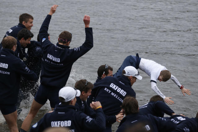 Members of the Oxford University rowing boat crew throw their cox Laurence Harvet into the River Thames as they celebrate their win against Cambridge University at the end of their 160th annual Boat Race on the River Thames, London, Sunday, April 6, 2014. The traditional boat race is a hotly contested point of honor between Oxford and Cambridge universities, and Cambridge still leads the series 81-78, with one tie. (AP Photo/Sang Tan)