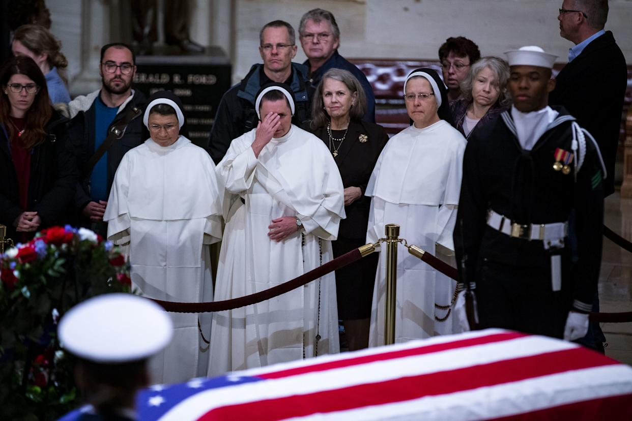 Members of the public, including nuns, pay their respects.