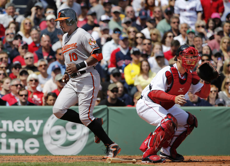 Baltimore Orioles' Adam Jones crosses the plate with a run, scoring on a double by Steve Clevenger during the third inning of a baseball game as Boston Red Sox catcher David Ross waits for the throw at Fenway Park in Boston Monday, April 21, 2014. (AP Photo/Winslow Townson)
