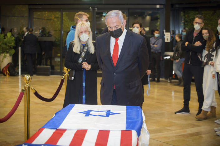 Israeli Prime Minister Benjamin Netanyahu stands before the casket of Sheldon Adelson, with his wife, Miriam Adelson, upon arrival to Ben Gurion Airport, near the city of Lod, Israel, Thursday, Jan. 14, 2021. Adelson, the billionaire mogul and power broker who built a casino empire spanning from Las Vegas to China and became a singular force in domestic and international politics has died after a long illness, his wife said Tuesday, Jan. 12, 2021. (Ami Shooman, Israel Hayom/ Pool Photo via AP)