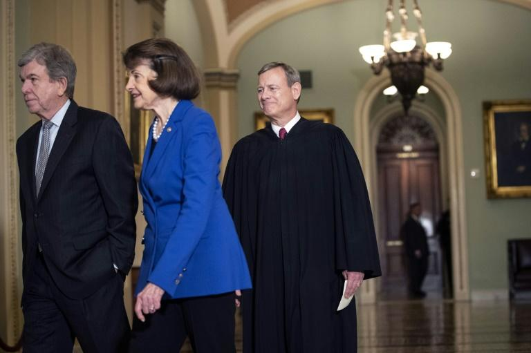 US Supreme Court Chief Justice John Roberts (R) arrives to administer the oath to senators who will serve as jurors at the impeachment trial of President Donald Trump