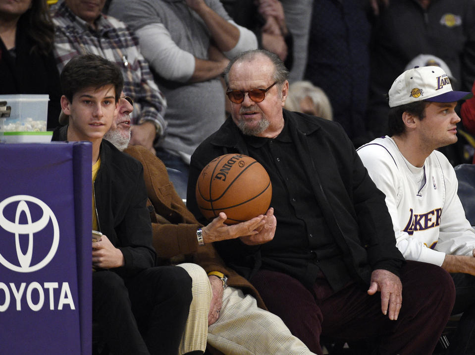 LOS ANGELES, CA - DECEMBER 18: Actor Jack Nicholson gives the game ball to record producer Lou Adler as they attend a basketball game between the Golden State Warriors and Los Angeles Lakers where Laker legend Kobe Bryant's jersey was retired at Staples Center on December 18, 2017 in Los Angeles, California. (Photo by Kevork S. Djansezian/Getty Images)