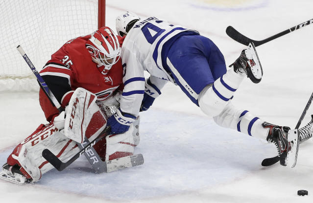 Toronto Maple Leafs' Nazem Kadri falls against Carolina Hurricanes goalie Curtis McElhinney (35) during the second period of an NHL hockey game in Raleigh, N.C., Wednesday, Nov. 21, 2018. (AP Photo/Gerry Broome)
