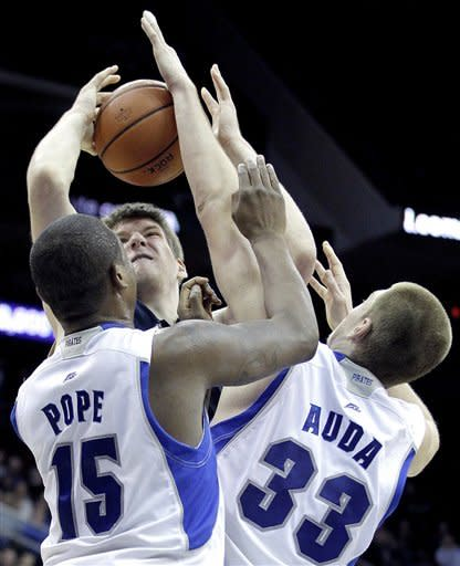 Notre Dame's Jack Cooley, center, tries to shoot against Seton Hall's Herb Pope (15) and Patrik Auda (33) during the second half of an NCAA college basketball game, Wednesday, Jan. 25, 2012, in Newark, N.J. Notre Dame won 55-42. (AP Photo/Julio Cortez)