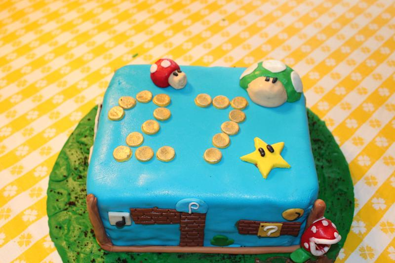 This undated photo provided by Justin Clark shows a Mario Brothers-themed square cake Clark made in Dallas. Clark, an amateur baker, typically uses a layer of fondant to cover a simple round cake, and gets creative from there. Shows like Ace of Cakes, Cake Boss, and various spinoffs tempt viewers with stunning visions of creations closer to art than dessert. This is the era of 3-D baking, and the simple, square birthday cake is little more than a remnant of the past. (AP Photo/Justin Clark)