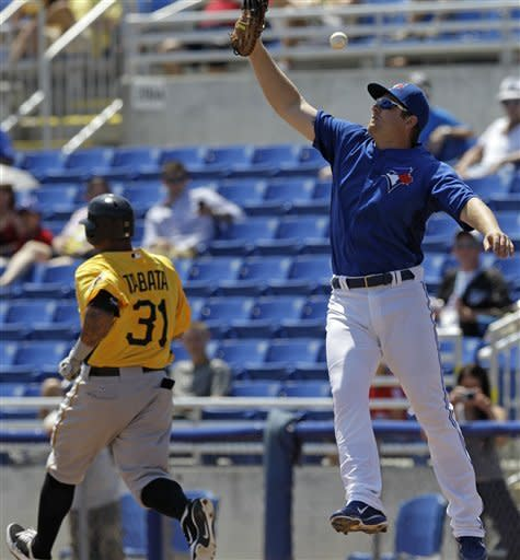 Toronto Blue Jays third baseman Brett Lawrie's fourth-inning errant throw sails past the glove of Blue Jays first baseman Adam Lind, right, on a single by Pittsburgh Pirates Jose Tabata, left, during their spring training baseball game in Dunedin, Fla., Sunday, April 1, 2012. Tabata reached second on the throwing error. (AP Photo/Kathy Willens)
