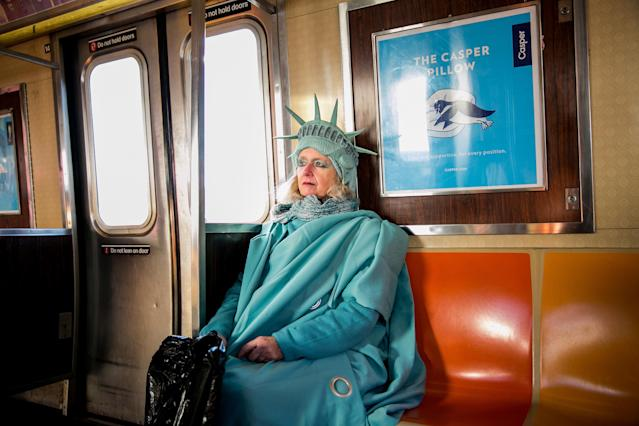 "<p>Lindley Hanlon rides the A train leaving John F. Kennedy International Airport, where she dressed as the Statue of Liberty to welcome people entering through Terminal 4 in Queens, N.Y., Feb. 6, 2017. While at the airport, law enforcement approached Hanlon and made her put away a sign that read ""Liberty and Justice for All."" Hanlon made her costume from Bed Bath and Beyond curtains and purchased the crown from a Halloween store in the East Village. ""I think it's more important than ever,"" she said about the Statue of Liberty. ""Because I think our liberties are threatened."" (Photograph by Sam Hodgson/The New York Times) </p>"