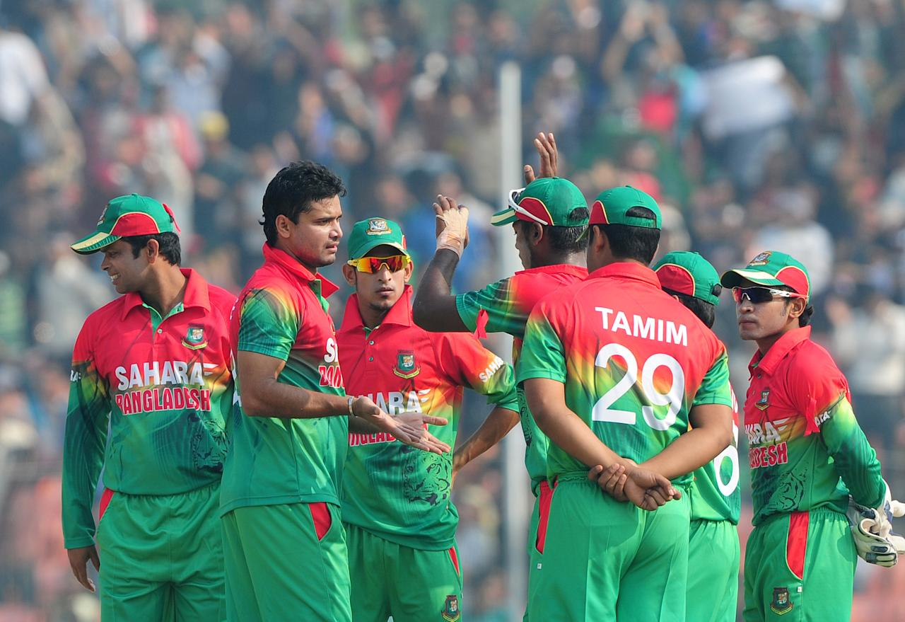 Bangladesh cricketer Mashrafe Bin Murtaza (2L) celebrates with teammates after the dismissal of the unseen West Indies batsman Lendl Simmons during the first one day international cricket match between Bangladesh and The West Indies at the Sheikh Abu Naser Stadium in Khulna on November 30, 2012.  AFP PHOTO/ Munir uz ZAMAN