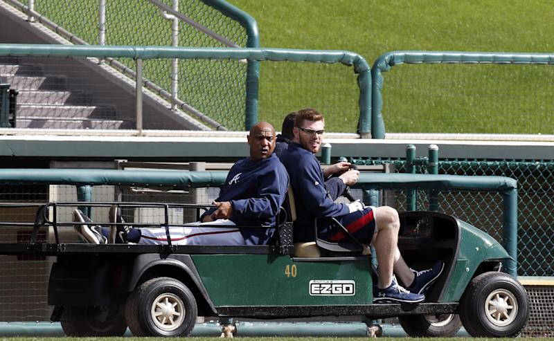 Atlanta Braves first base coach Terry Pendleton, left, and Atlanta Braves first baseman Freddie Freeman, front, ride a cart to the batting cages during a spring training baseball workout, Thursday, Feb. 13, 2014, in Kissimmee, Fla. (AP Photo/Alex Brandon)
