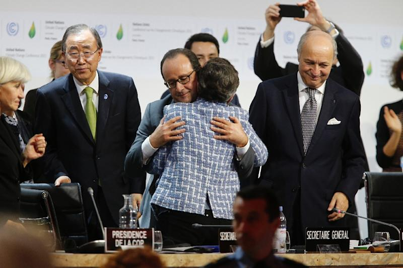 Executive Secretary of the UNFCCC Christiana Figueres (C) and France's President Francois Hollande hug in Le Bourget on December 12, 2015 (AFP Photo/Francois Guillot)