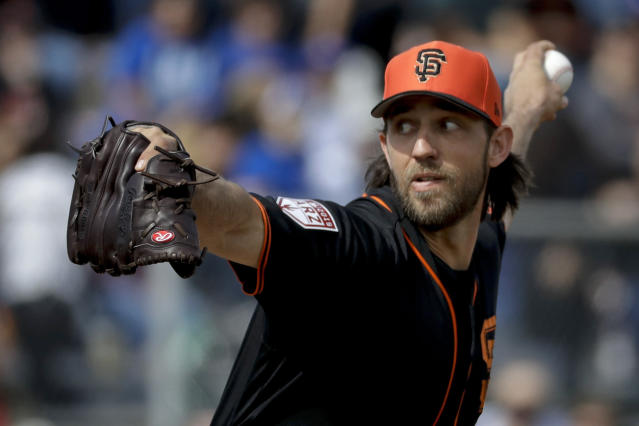 FILE - In this Feb. 24, 2019, file photo, San Francisco Giants starting pitcher Madison Bumgarner throws against the Chicago Cubs during the first inning of a spring baseball game in Scottsdale, Ariz. Bumgarner insists he is never one to live in the past, but always stays in the moment. So, the frustrations of his past two injury-shortened seasons are hardly on his mind. But the 2014 World Series MVP sure would like to return to the 200-inning pitcher he has long been when healthy. (AP Photo/Chris Carlson, File)