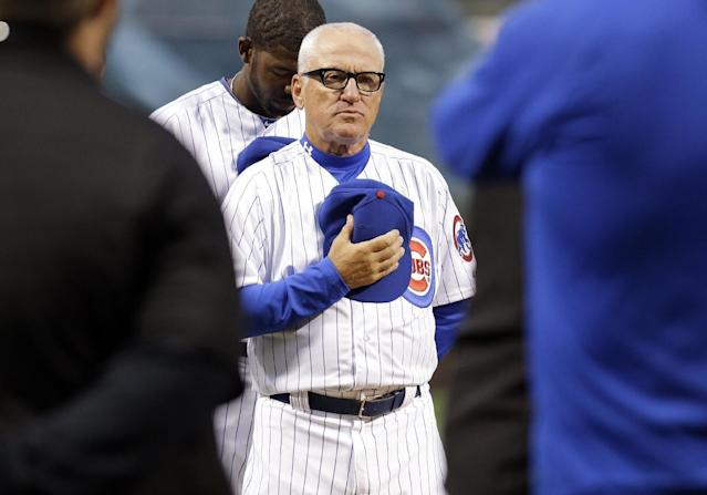 Chicago Cubs manager Joe Maddon stands for a tribute to Ernie Banks before a Major League Baseball season-opening game against the St. Louis Cardinals in Chicago, Sunday, April 5, 2015. (AP Photo/Nam Y. Huh)
