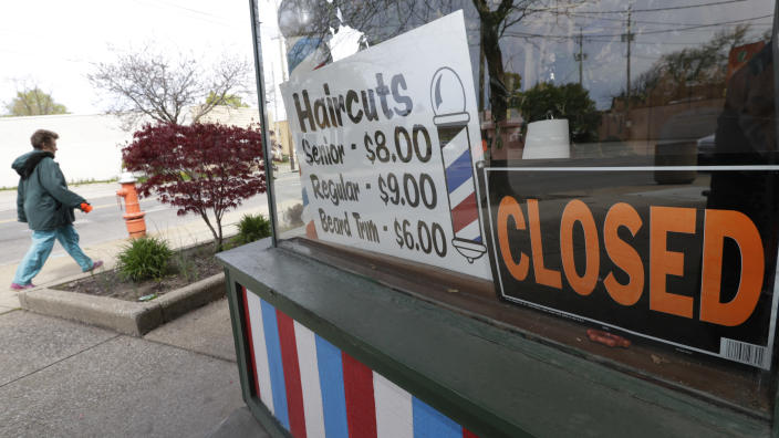 FILE - In this May 6, 2020 file photo, a woman walks past a closed barber shop in Cleveland. Small businesses are in limbo again as the coronavirus outbreak rages and the government's $659 billion relief program draws to a close. Companies still struggling with sharply reduced revenue are wondering if Congress will give them a second chance at the Paycheck Protection Program, which ends Friday, Aug. 7, after giving out 5.1 million loans worth $523 billion. (AP Photo/Tony Dejak, File)