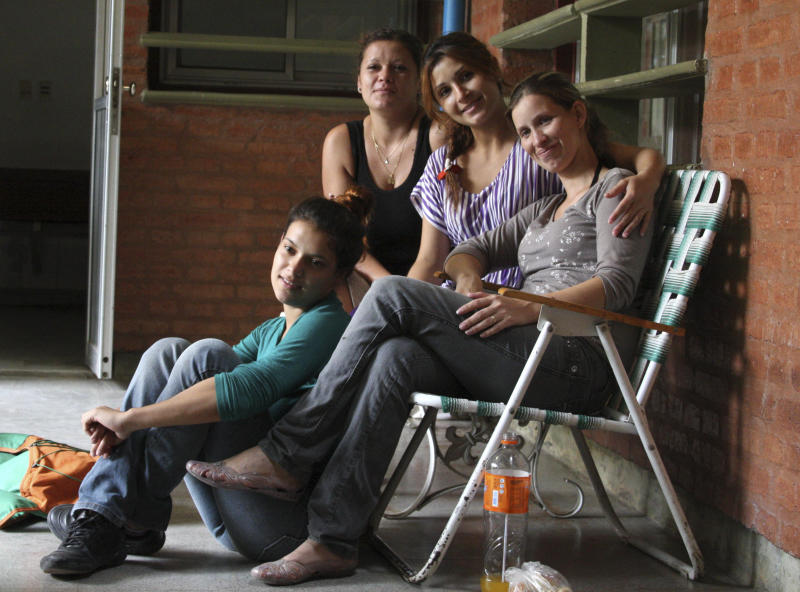 Analia Bouter, right, poses for a photo with friends outside the hospital in Resistencia, Argentina, Wednesday April 11, 2012. Bouter found her baby alive in a coffin in the morgue nearly 12 hours after the girl had been declared dead. The tiny girl, born three months premature, was in critical but improving condition Wednesday in the same hospital where the staff pronounced her stillborn on April 3. (AP Photo/Juan Pablo Faccioli)