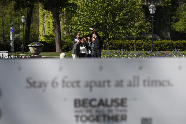 """A group of visitors take a selfie near a sign reading """"stay 6 feet apart at all times,"""" Thursday, May 6, 2021, on the University of Chicago campus in Chicago. Even as restrictions relax across much of the United States, colleges and universities have taken new steps to police campus life as the virus spreads through students who are among the last adults to get access to vaccines. (AP Photo/Shafkat Anowar)"""