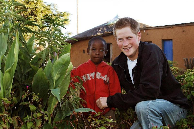 Harry and Mutsu with a tree they planted in the grounds of the Mants'ase childrens home in March 2004 (PA Archive/PA Images)