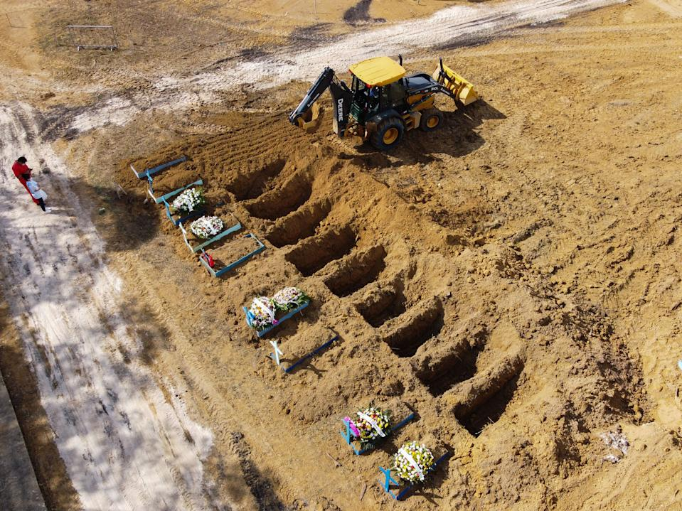 Aerial view showing a tractor digging graves in a new area of the Nossa Senhora Aparecida cemetery reserved for COVID-19 victims as a burial takes place, in Manaus, Brazil, taken on January 8, 2021 amid the novel coronavirus pandemic. (Photo by Michael DANTAS / AFP) (Photo by MICHAEL DANTAS/AFP via Getty Images)