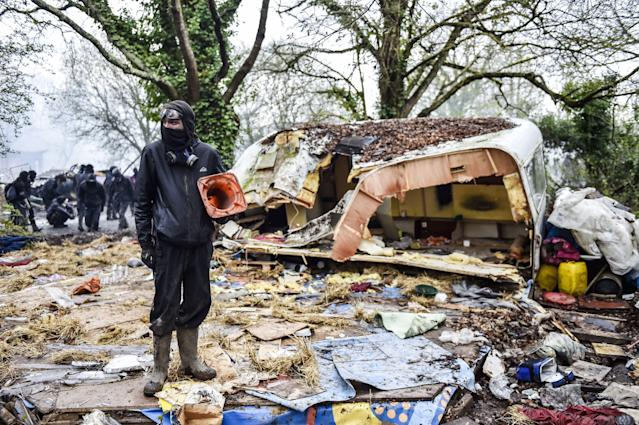 <p>A protester stands in the rubble destroyed houses on April 10, 2018 during a police operation to raze the decade-old camp known as ZAD (Zone a Defendre – Zone to defend) at Notre-Dame-des-Landes, near the western city of Nantes, and evict the last of the protesters who had refused to leave despite the government agreeing to ditch a proposed airport. (Photo: Loic Venance/AFP/Getty Images) </p>