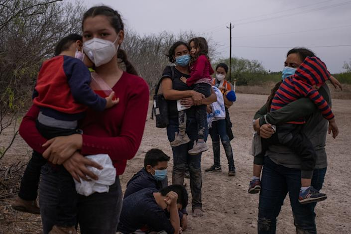 Asylum seeking migrant mothers from Central America hold their children as they await transport after crossing the Rio Grande river into the United States from Mexico on a raft in La Joya, Texas, U.S., March 14, 2021. (Adrees Latif/Reuters)