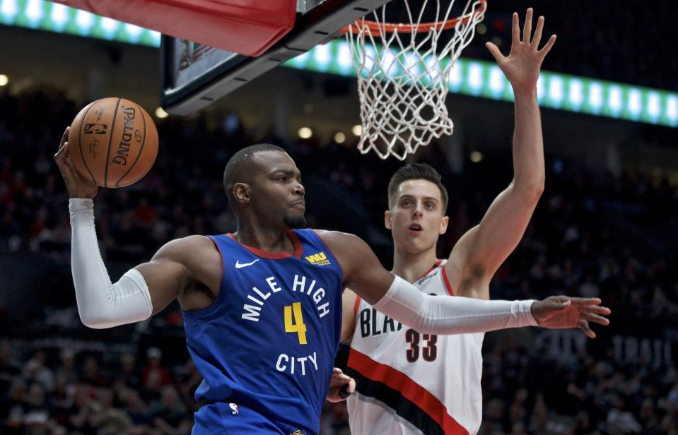 Denver Nuggets forward Paul Millsap, left, looks to pass the ball around Portland Trail Blazers forward Zach Collins during the first half of Game 6 of an NBA basketball second-round playoff series Thursday, May 9, 2019, in Portland, Ore. (AP Photo/Craig Mitchelldyer)