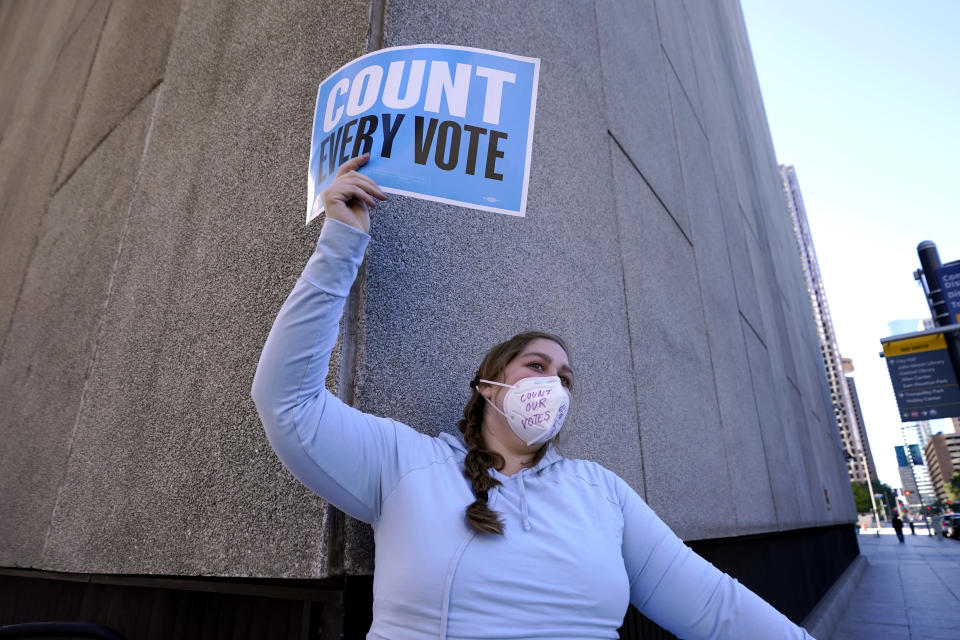Victoria Houptman-Bryan joins demonstrators as they stand across the street from the federal courthouse in Houston, Monday, Nov. 2, 2020, before a hearing in federal court involving drive-thru ballots cast in Harris County. The lawsuit was brought by conservative Texas activists, who have railed against expanded voting access in Harris County, in an effort to invalidate nearly 127,000 votes in Houston because the ballots were cast at drive-thru polling centers established during the pandemic. (AP Photo/David J. Phillip)