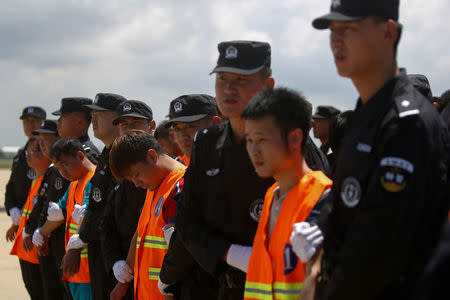 Chinese nationals (in orange vests) who were arrested over a suspected internet scam, are escorted by Chinese police officers before they were deported at Phnom Penh International Airport, in Phnom Penh, Cambodia, October 12, 2017. REUTERS/Samrang Pring