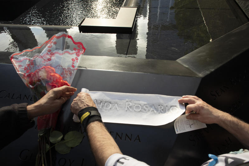 Louis Gonzalez makes a rubbing of his sister's name at the National September 11 Memorial, Wednesday, Sept. 11, 2019 in New York. Aida Rosario was killed during the attacks of Sept. 11, 2001. (AP Photo/Mark Lennihan)