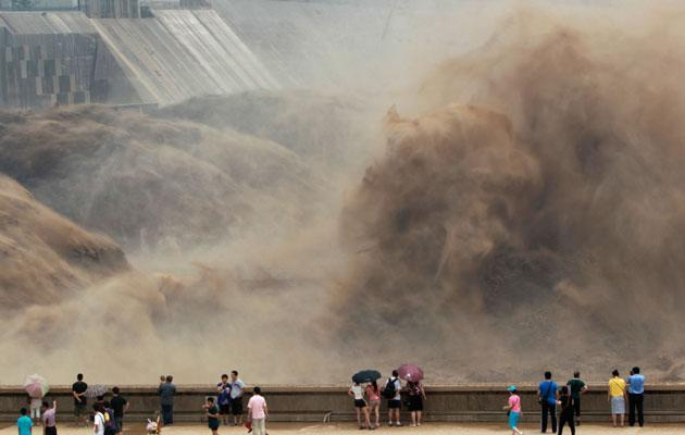 Local residents watch as sediment-laden flood water gushes through the Xiaolangdi Dam on the Yellow River in Luoyang, Henan province July 6, 2012. Picture taken July 6, 2012. REUTERS/Carlf Zhang