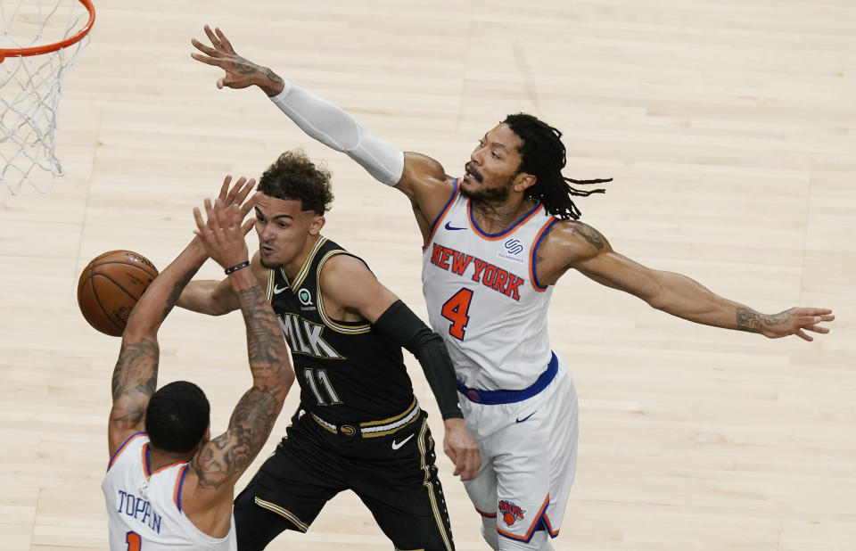 Atlanta Hawks' Trae Young (11) passes the ball against New York Knicks' Derrick Rose (4) and Obi Toppin (1) during the first half in Game 4 of an NBA basketball first-round playoff series Sunday, May 30, 2021, in Atlanta. (AP Photo/Brynn Anderson)