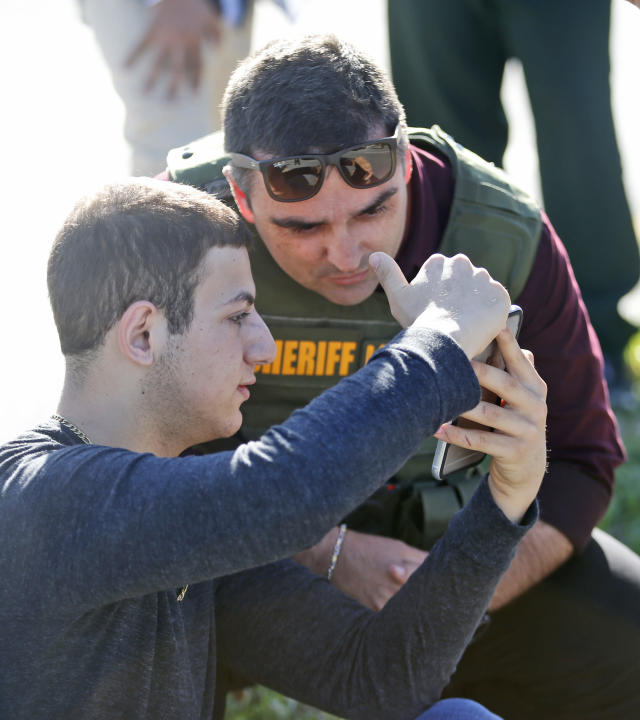 <p>A student shows a law enforcement officer a photo or video from his phone, Wednesday, Feb. 14, 2018, in Parkland, Fla. A shooting at Marjory Stoneman Douglas High School sent students rushing into the streets as SWAT team members swarmed in and locked down the building. Police were warning that the shooter was still at large even as ambulances converged on the scene and emergency workers appeared to be treating those possibly wounded. (Photo: Wilfredo Lee/AP) </p>