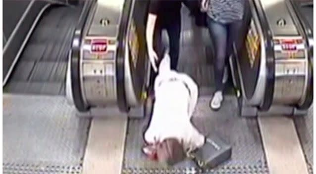 A woman distracted by her phone falls over at the top of an escalator. Source: 7 News