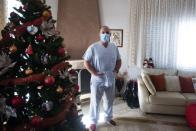 In this Saturday, Dec. 12, 2020 photo, Gabriel Tachtatzoglou poses at his home in Agios Athanassios, outside Thessaloniki city, northern Greece. Tachtatzoglou has worked as an ICU nurse in northern Greece for 20 years but when the pandemic struck his city in the fall, COVID-19 wards were quickly overwhelmed. He saw little choice other than to treat sick members of his family at home, setting up a treatment site with borrowed and rented medical machinery and using a hat stand to hold IV bags. (AP Photo/Giannis Papanikos)