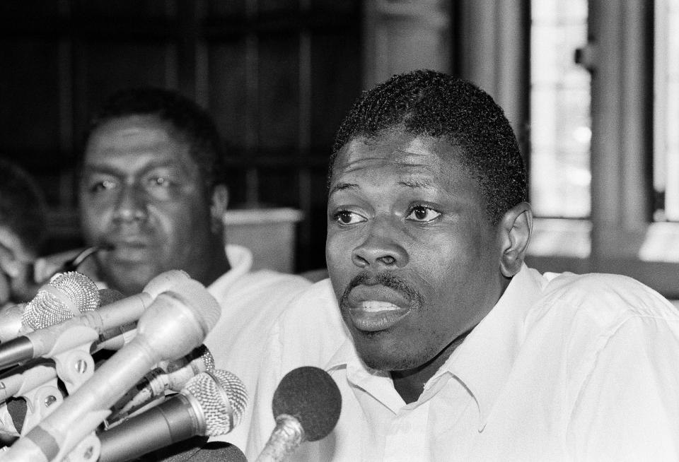 Patrick Ewing talks with reporters in 1985 with John Thompson in the background.