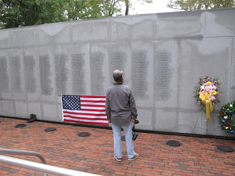 """Former Marine Ed Ayers of Scranton, Penn., stares at the names on the Beirut Bombing Memorial in Jacksonville, N.C., on Wednesday, Oct. 23, 2013. Wednesday was the 30th anniversary of a terrorist bombing that killed 241 U.S. service members. Ayers, who did two tours in Lebanon, said the peacekeeping mission there was worth it but, """"I wish it was handled differently."""" (AP Photo/Allen G. Breed)"""