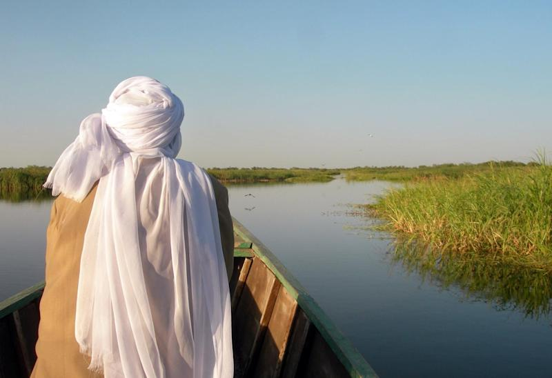 A man sits on a boat in Lake Chad on December 8, 2009