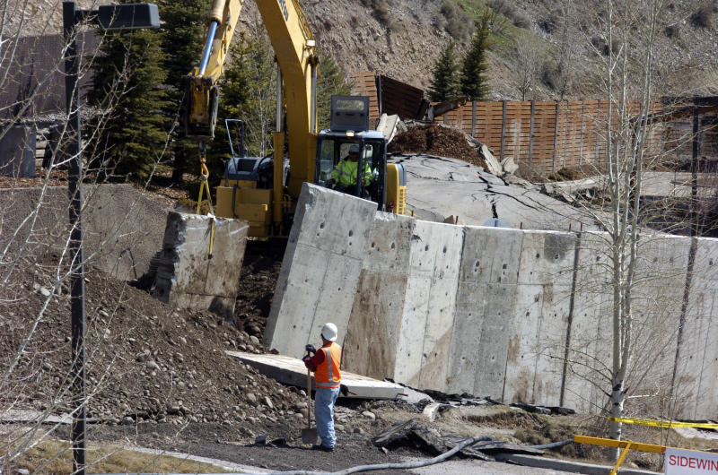 A work crew moves a concrete barrier that failed to stop a slow-motion landslide in Jackson, Wyo., as houses and businesses in the slide zone remained at risk on Saturday, April 19, 2014. No one can say when the mountainside collapsing into this Wyoming resort town will give way. But it appears increasingly likely that when it does, it's going to take a piece of Jackson with it. (AP Photo/Matthew Brown)
