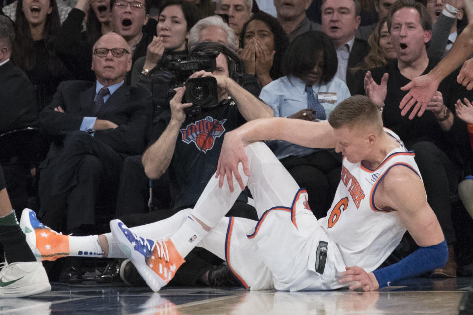 Knicks forward Kristaps Porzingis clutches his knee in the first half Tuesday night. (AP)