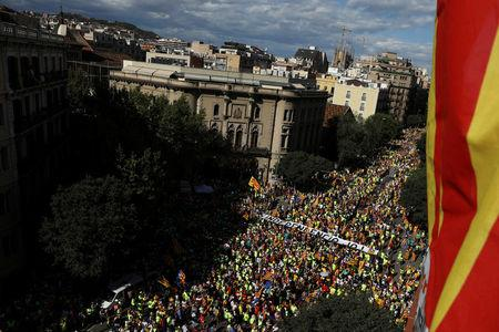 """A banner reading """"Independence Now"""" is carried as thousands of people gather for a rally on Catalonia's national day 'La Diada' in Barcelona, Spain, September 11, 2017. REUTERS/Susana Vera"""