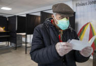A Lithuanian man reads a ballot paper at a polling station during the second round of a parliamentary election in Vilnius, Lithuania, Sunday, Oct. 25, 2020. Polls opened Sunday for the run-off of national election in Lithuania, where the vote is expected to bring about a change of government following the first round, held on Oct. 11, which gave the three opposition, center-right parties a combined lead. (AP Photo/Mindaugas Kulbis)