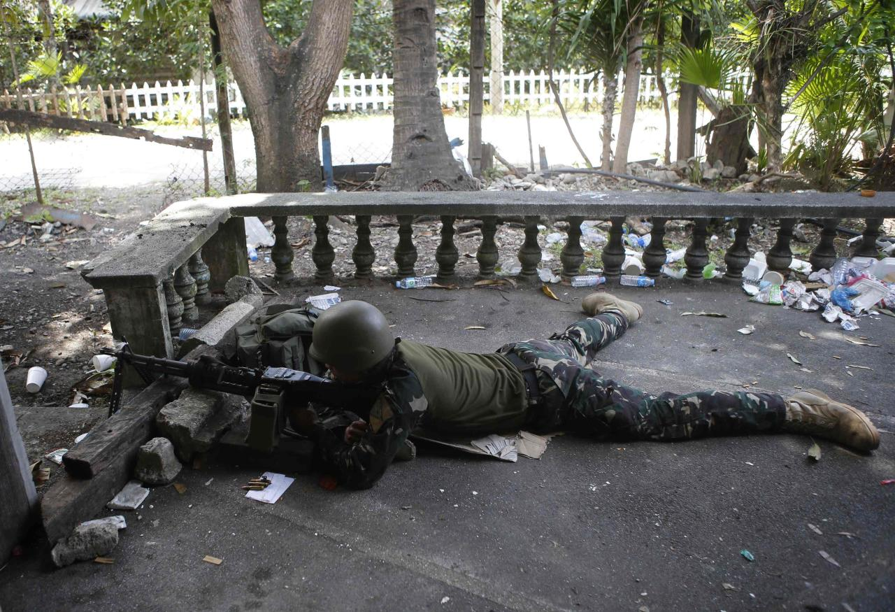 A government soldier takes a position with a machinegun at the porch of a house during fighting with Muslim rebels from the Moro National Liberation Front (MNLF) in Zamboanga city, southern Philippines, September 15, 2013. A week of violence in the southern Philippines has undercut hopes of lasting peace in the resource-rich region and exposed the government to criticism for underestimating rogue Muslim rebels who feel ignored by a landmark deal last year. REUTERS/Erik De Castro (PHILIPPINES - Tags: CIVIL UNREST CONFLICT POLITICS)