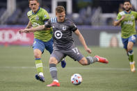 Minnesota United midfielder Robin Lod (17) kicks the ball in front of Seattle Sounders defender Shane O'Neill, left, during the first half of an MLS soccer match Friday, April 16, 2021, in Seattle. (AP Photo/Ted S. Warren)